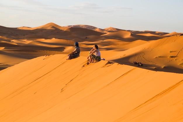 Colpo lungo estremo di due genti che si siedono in cima alla duna Foto Gratuite
