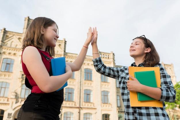 Colpo medio basso angolo di ragazze ad alto fiving Foto Gratuite