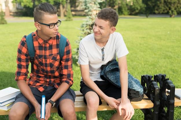 Colpo medio dei ragazzi della high school che si siedono sul banco Foto Gratuite
