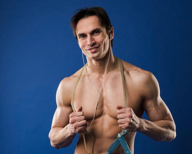 Colpo medio dell'uomo atletico senza camicia di smiley con le cuffie Foto Gratuite