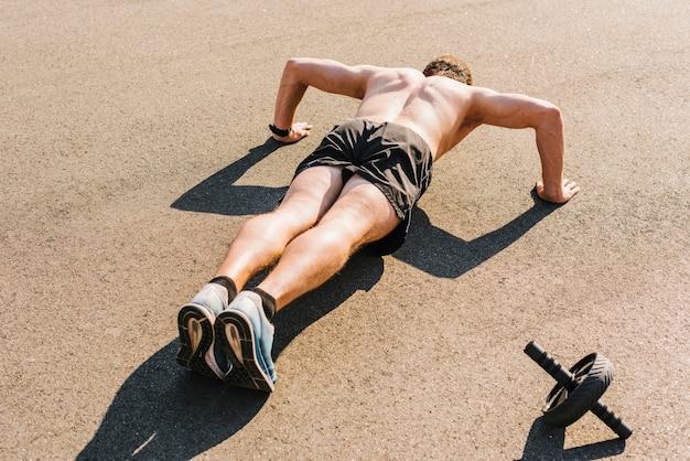 Colpo medio dell'uomo che fa i push-up Foto Gratuite