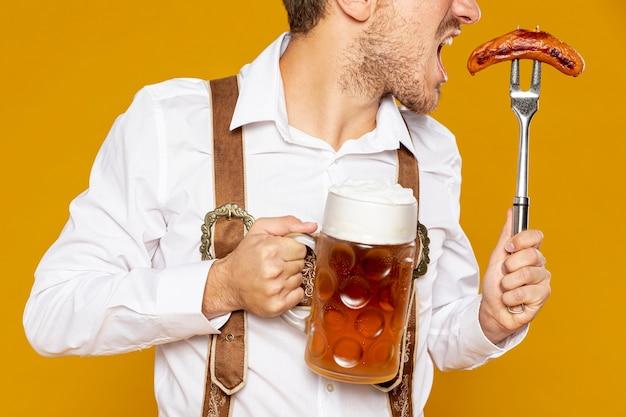 Colpo medio dell'uomo che tiene la pinta di birra Foto Gratuite
