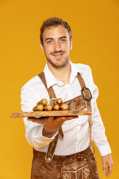 Colpo medio dell'uomo con il vassoio di salsiccie Foto Gratuite