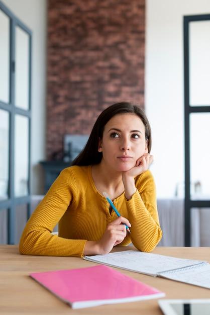 Colpo medio della donna che si domanda mentre lavora Foto Gratuite