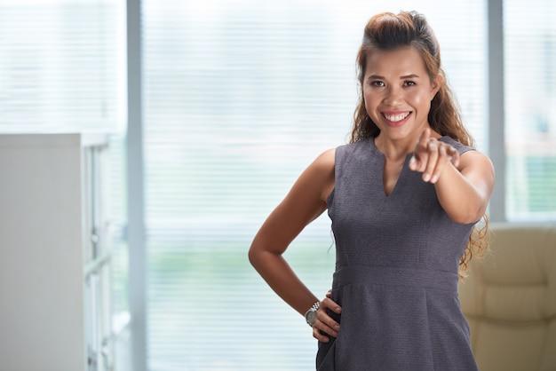 Colpo medio della donna di affari che indica alla macchina fotografica e sorridere Foto Gratuite