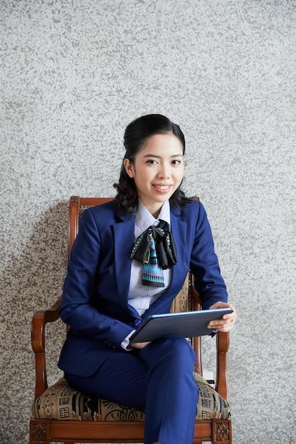 Colpo medio della donna etnica di affari che si siede con il pc della compressa accanto alla parete grigia Foto Gratuite