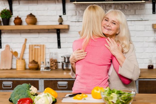 Colpo medio della madre che abbraccia sua figlia Foto Gratuite