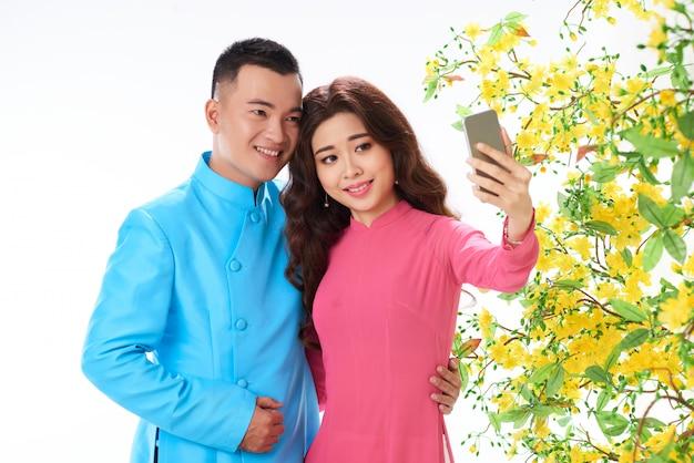 Colpo medio delle coppie asiatiche che prendono il selfie di festival di primavera Foto Gratuite
