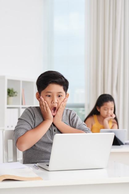Colpo medio di alunni asiatici in aula che lavorano ai computer portatili, un ragazzo nella parte anteriore con un'espressione sorpresa sul viso Foto Gratuite