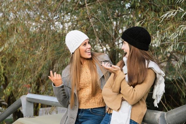 Colpo medio di due donne che parlano nel parco Foto Gratuite