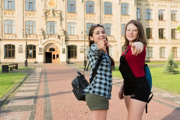 Colpo medio di due ragazze del liceo che indicano alla macchina fotografica Foto Gratuite