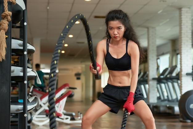 Colpo medio di giovane sportiva che fa esercizio della corda del crossfit Foto Gratuite