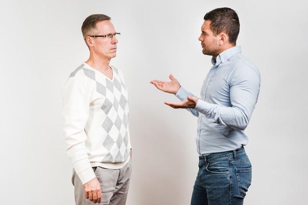 Colpo medio di padre e figlio a parlare Foto Gratuite