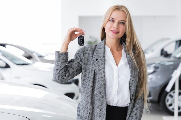 Colpo medio di una donna bionda che tiene una chiave dell'automobile Foto Gratuite