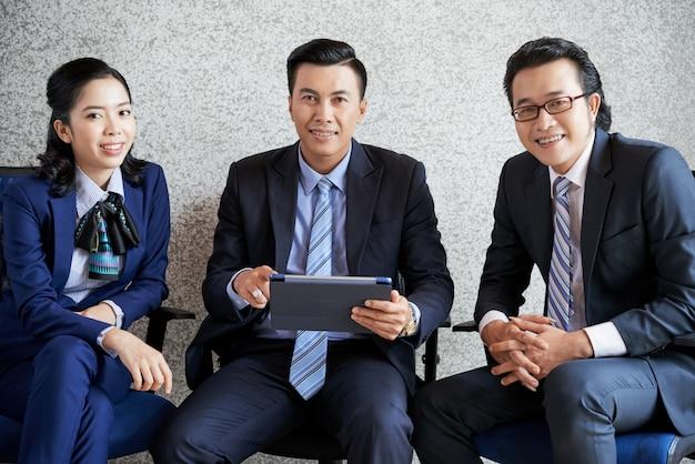 Colpo medio di una squadra di affari che si siede nell'ufficio con il pc della compressa Foto Gratuite