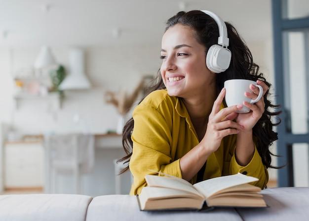Colpo medio donna con cuffie e libro Foto Gratuite