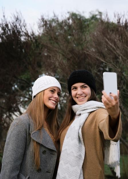 Colpo medio due donne sorridenti prendendo un selfie Foto Gratuite