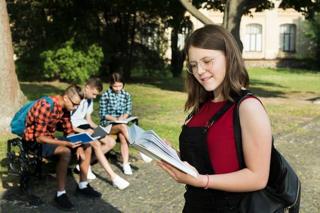 Colpo medio obliquamente della ragazza del highshool che legge un libro Foto Gratuite