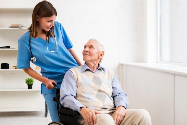 Colpo medio vecchio in sedia a rotelle guardando infermiera Foto Gratuite