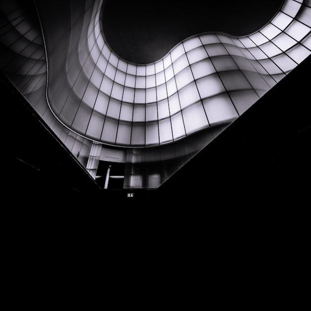 Colpo monocromatico verticale di una costruzione architettonica astratta Foto Gratuite