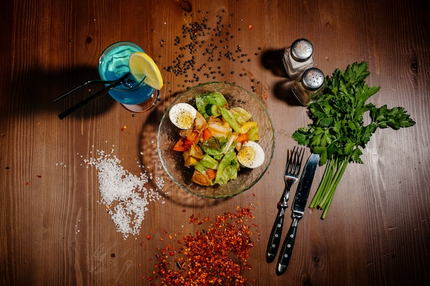 Colpo orizzontale di grande ciotola bianca di insalata dell'uovo alla diavola su di legno scuro Foto Premium