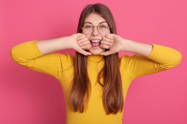 Colpo orizzontale di magnetica adorabile ragazza giovane apertura bocca ampiamente, guardando direttamente mettendo vicino al viso Foto Gratuite
