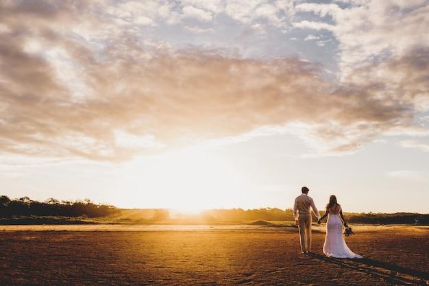 Colpo orizzontale di un uomo e una donna in abiti da sposa che tengono le mani durante il tramonto Foto Gratuite