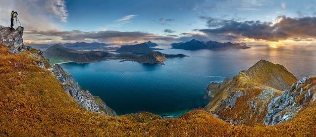 Colpo panoramico della collina veggen vicino al mare sotto un cielo blu in norvegia Foto Gratuite