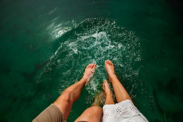 Colpo piatto laici delle coppie che giocano in acqua con i piedi Foto Gratuite