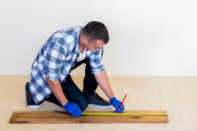 Colpo pieno dell'uomo che prende misura su legno Foto Gratuite