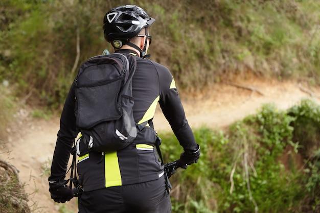 Colpo posteriore del motociclista in abbigliamento da ciclismo nero e giallo, casco e zaino in sella a mountain bike elettrica su pista durante l'allenamento all'aperto nel fine settimana. persone, stile di vita sano e concetto di sport Foto Gratuite