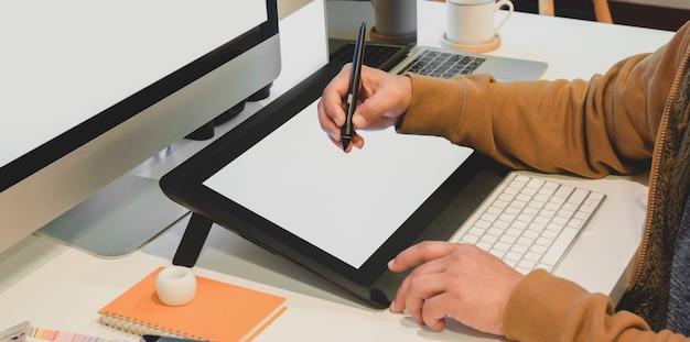 Colpo potato del progettista maschio che pubblica il suo progetto sulla compressa digitale dello schermo in bianco nel suo ufficio moderno Foto Premium