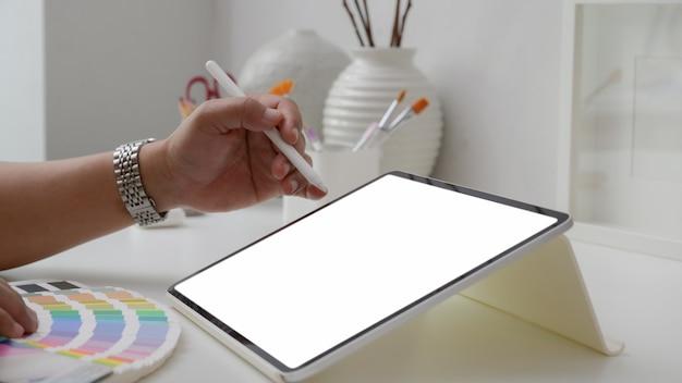 Colpo potato del progettista maschio che sceglie colore sul campione di colore mentre lavorando alla compressa dello schermo in bianco Foto Premium