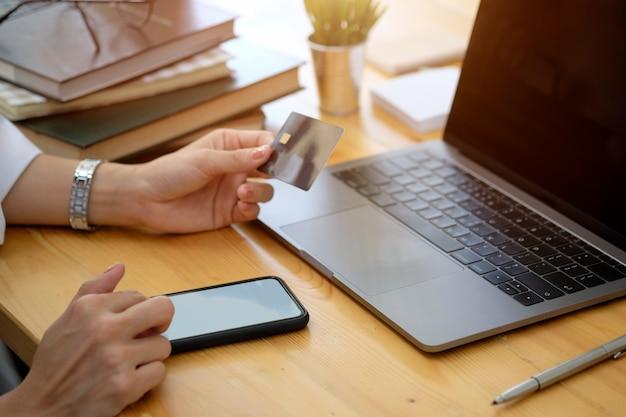 Colpo potato della mano femminile che tiene la carta di credito di plastica e che per mezzo dello smart phone allo scrittorio in ufficio. concetto di pagamento dello shopping online. Foto Premium