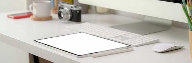 Colpo ritagliato di comoda scrivania con dispositivi tablet e computer schermo vuoto Foto Premium