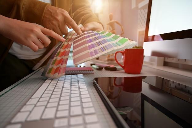 Colpo ritagliato di designer grafico creativo che lavora sulla selezione dei colori e sui campioni di colore Foto Premium