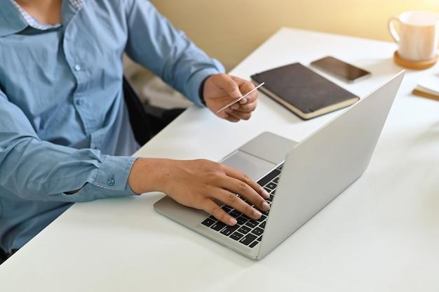 Colpo ritagliato di informazioni di carta di credito di input dell'uomo durante lo shopping online. Foto Premium