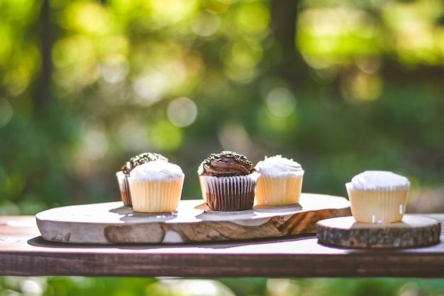 Colpo selettivo del primo piano dei bigné della crema e del cioccolato su una superficie di legno Foto Gratuite