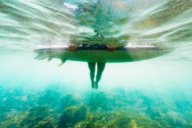 Colpo subacqueo di donna con tavola da surf Foto Gratuite