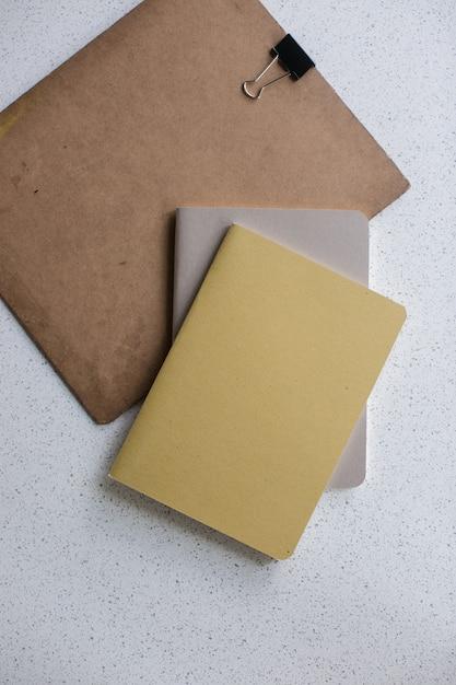 Colpo verticale dell'angolo alto dei taccuini marroni e grigi e di un bordo su una superficie bianca Foto Gratuite