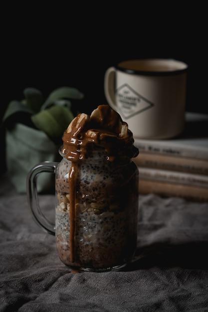 Colpo verticale dell'angolo alto di una bevanda deliziosa della banana e del cioccolato con i semi di chia Foto Gratuite
