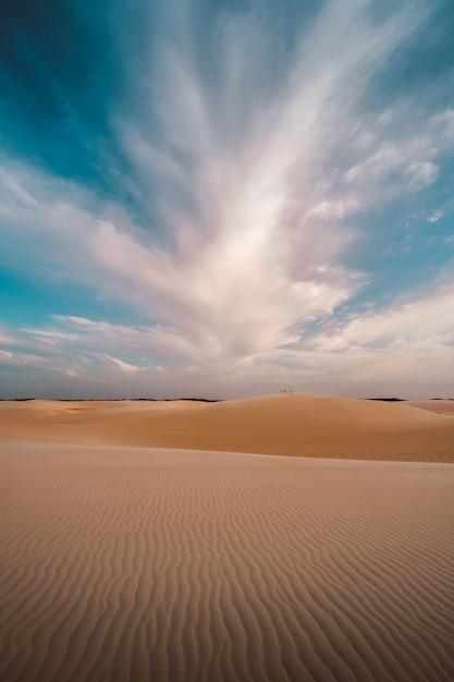 Colpo verticale delle colline sabbiose sotto le belle nuvole nel cielo Foto Gratuite