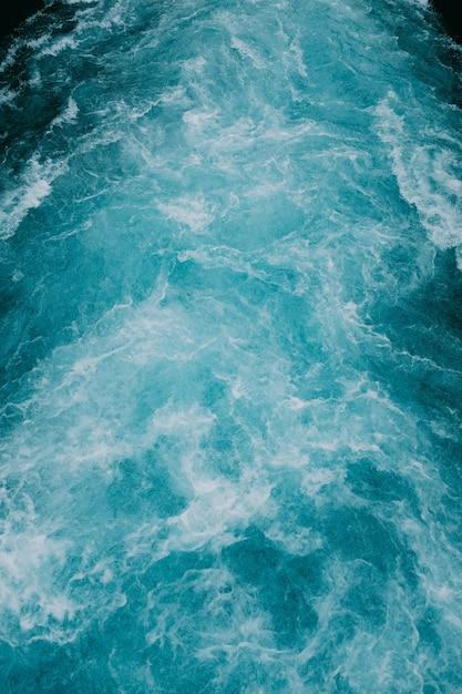 Colpo verticale delle onde schiumose dell'acqua nel mare Foto Gratuite