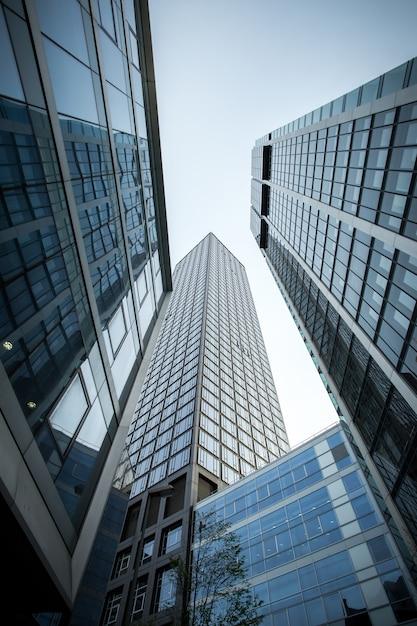 Colpo verticale di angolo basso dei grattacieli di aumento in una facciata di vetro a francoforte, germania Foto Gratuite