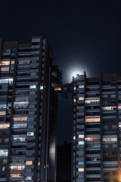 Colpo verticale di bellissimi condomini collegati con un breve ponte sotto il cielo stellato Foto Gratuite