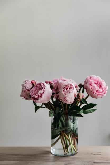 Colpo verticale di peonie rosa con foglie verdi in un vaso di vetro Foto Gratuite