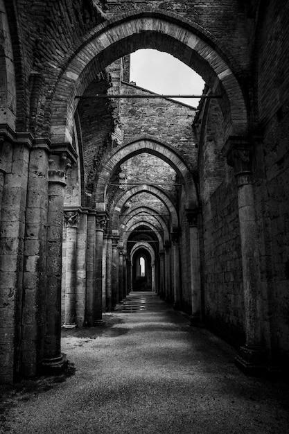 Colpo verticale di un corridoio con pilastri e porte ad arco ad abbazia di san galgano Foto Gratuite