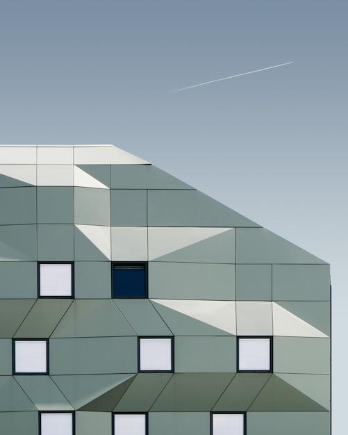Colpo verticale di un edificio geometrico sotto il cielo blu Foto Gratuite