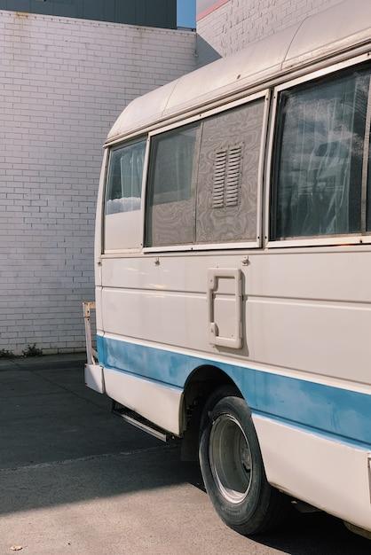 Colpo verticale di un furgone bianco e blu parcheggiato fuori durante il giorno Foto Gratuite