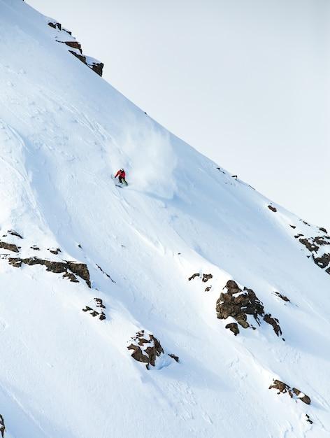 Colpo verticale di una corsa con gli sci maschio sulla montagna coperta di neve in inverno Foto Gratuite